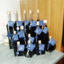 v steklenicah borovničevo vino, zvezdica je iz das mase, v ozadju je v stekleni posodi dom