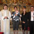 ati, mami, botrca me drži v naročju in gospod kaplan, ki me je krstil
