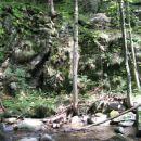 Nad njim lahko prečiš potok in točno v sredini  splezaš na poševno polico in levo navzgor,
